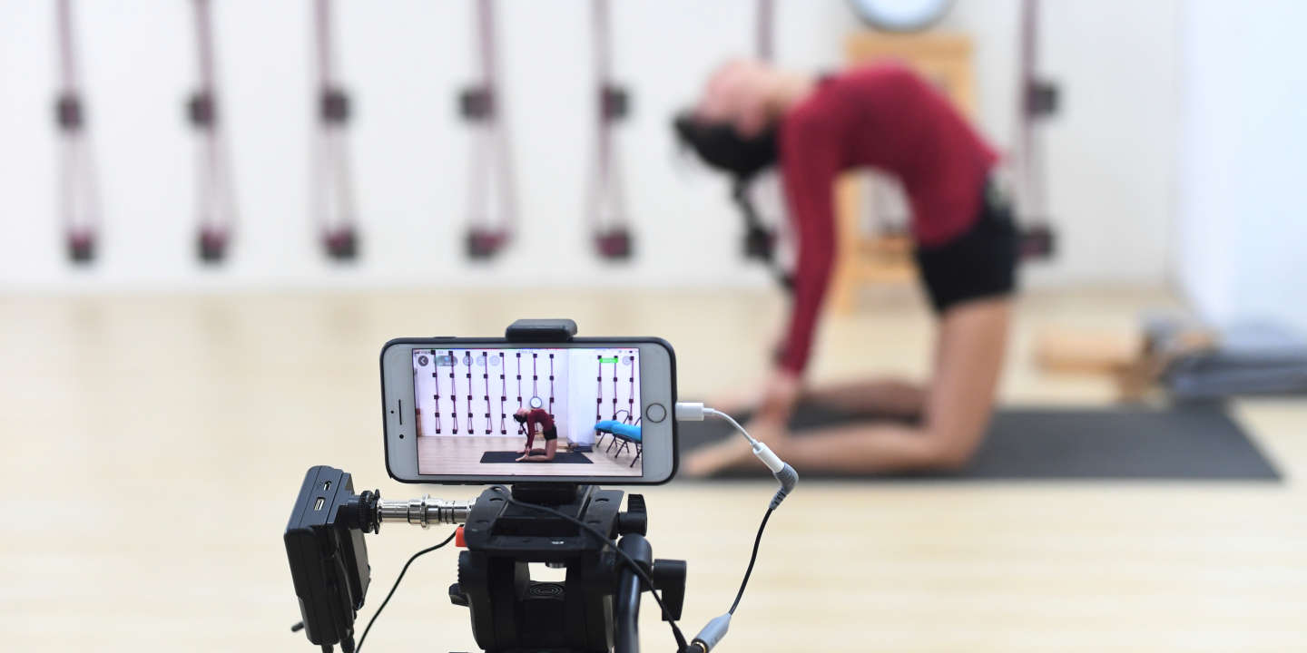 An instructor does a live broadcast of her yoga lesson with a mobile phone as the yoga academy offers free online classes following the outbreak of the novel coronavirus, in Guangzhou, Guangdong province, China February 7, 2020. Picture taken February 7, 2020. cnsphoto via REUTERS   ATTENTION EDITORS - THIS IMAGE WAS PROVIDED BY A THIRD PARTY. CHINA OUT. - RC26WE90MNZM