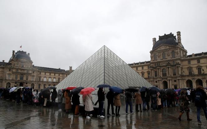 Des gens font la queue devant le Louvre alors que le personnel a fermé le musée en raison de l'épidémie de coronavirus, le 1er mars.