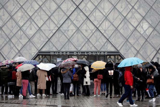 Des touristes attendent devant le Louvre, à Paris, le 2mars2020, alors que lessalariés ont voté à nouveau en assemblée générale pour exercer un droit de retrait, s'estimant menacés par l'épidémie du nouveau coronavirus.