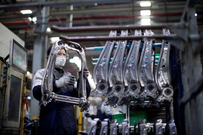 Un employé d'une usine de Shanghaï équipé d'un masque, le 24 février.