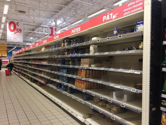 Dans les rayons de pâtes du supermarché Auchan près de Creil, les étagères éparses témoignent de la ruée quotidienne de clients pour se procurer ces denrées.