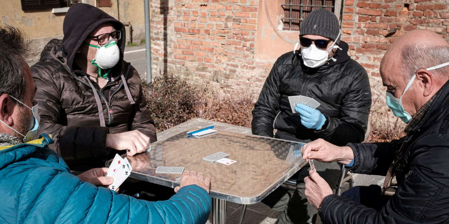 Life inside a red zone: A group of men wearing protective masks play a game of cards out on a street in San Fiorano, one of the towns on lockdown due to a coronavirus outbreak, in this picture taken by schoolteacher Marzio Toniolo in San Fiorano, Italy, February 27, 2020. Picture taken February 27, 2020. Marzio Toniolo/via REUTERS THIS IMAGE HAS BEEN SUPPLIED BY A THIRD PARTY. MANDATORY CREDIT