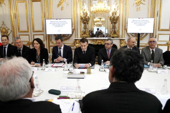 Le ministre de la santé, Olivier Véran (à gauche), et Emmanuel Macron lors d'une réunion avec des chercheurs sur le Covid-19, à l'Elysée, le 5 mars.