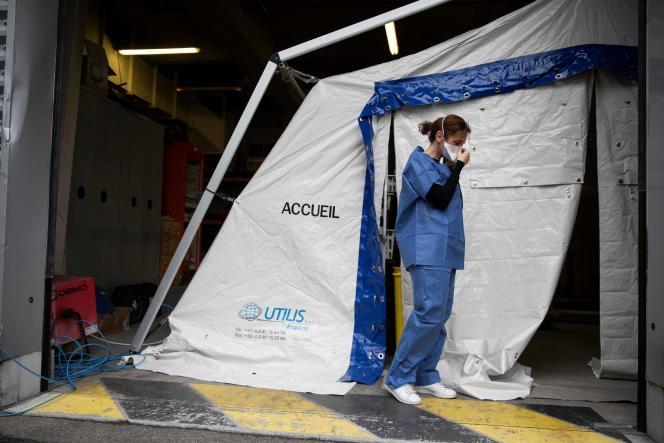Un personnel hospitalier devant une tente installée pour dépister le Covid-19 dans la cour de l'hôpital Henri-Mondor, à Créteil, le 6 mars.