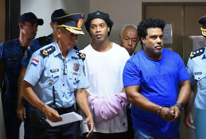 Le footballeur brésilien à la retraite Ronaldinho, au centre, et son frère Roberto Assis arrivent au palais de justice d'Asunción, le 7 mars, pour comparaître devant un procureur qui décidera de leur remise en liberté sous caution ou non à la suite de leur entrée irrégulière au Paraguay.