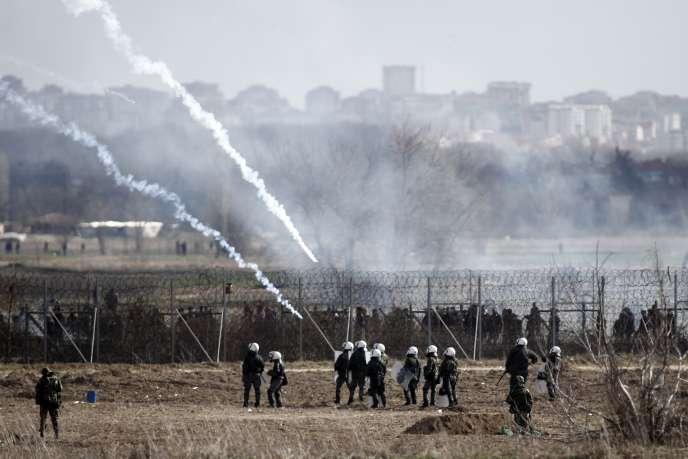 Des policiers et gardes-frontières grecs face à des réfugiés tentant de traverser la frontière avec la Turquie, dans la ville de Kastanies, le 7mars.