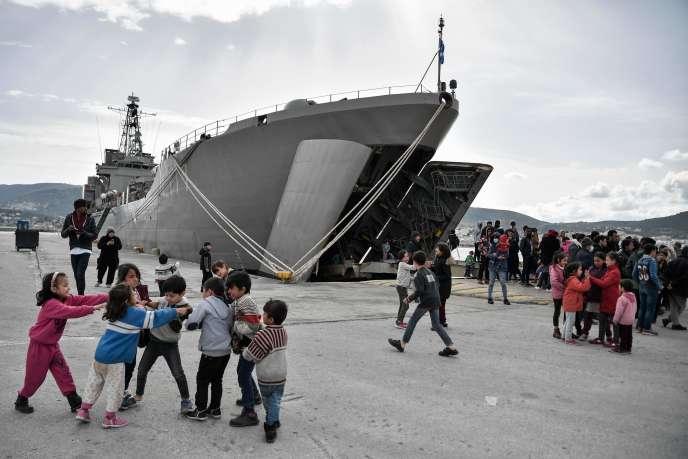 Des enfants jouent devant le navire qui accueille les réfugiés arrivés dans le port de Mytilène,sur l'île de Lesbos, le 7mars.