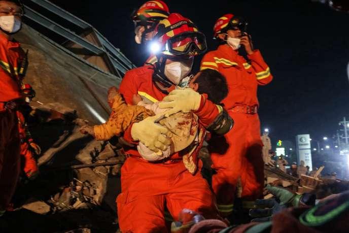 Un enfant sauvé des décombres après l'effondrement d'un hôtel àQuanzhou, où des personnes étaient placées en quarantaine, le 8 mars.