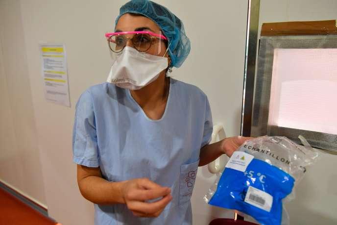 Une infirmière du CHU de Bordeaux transporte des échantilons prélevés sur des patients, le 9 mars.