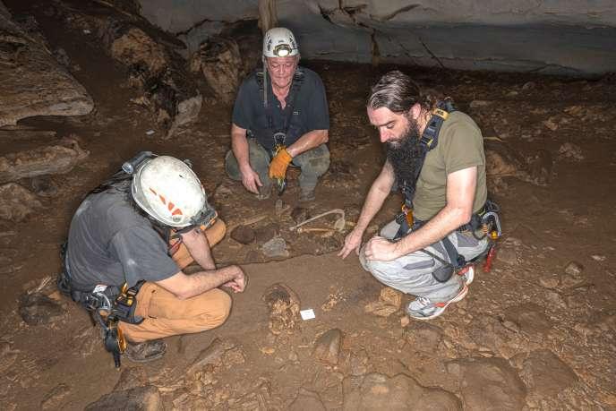 De gauche à droite : les chercheurs Sébastien Villote, Richard Oslisly et Sacha Kacki devant les restes d'un crâne dans la grotte d'Iroungou, au Gabon, le 3mars 2020.