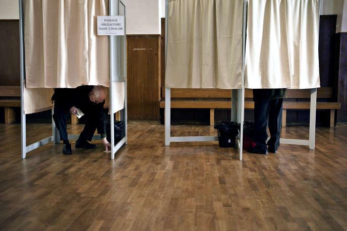 Des personnes choisissent leur bulletin de vote dans les isoloirs, le 20 mars 2011, dans un bureau de vote de Dijon, lors des élections cantonales.