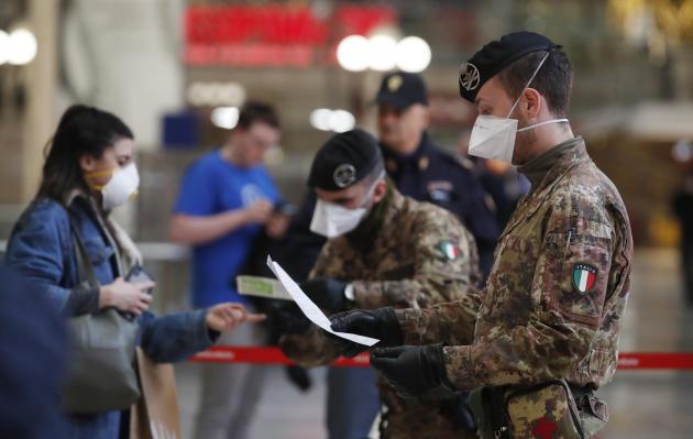 Des militaires contrôlent des passagers, à la gare de Milan, lundi 9mars.