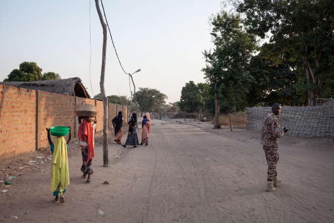 Des femmes et un combattant d'un groupe armé marchent sur une route à Birao, dans le nord de la Centrafrique, en décembre 2017.