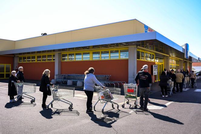 File d'attente devant un supermarché dans la banlieue de Rome, le 11 mars.