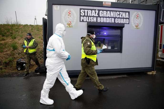 Les autorités polonaises équipées pour effectuer des contrôles sanitaires sur les passagers des véhicules, à la frontière avec l'Allemagne, le 9 mars.