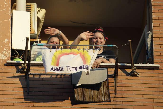 Des adolescentes vivant à Rome ont accroché à leur balcon un drapeau aux couleurs de l'arc-en-ciel avec un texte disant« Tout ira bien», le 15 mars.