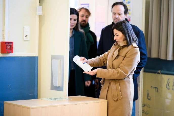 La maire PS de Paris, Anne Hidalgo, utilisant de gel hydroalcoolique, le 15 mars, lors du premier tour des élections municipales.