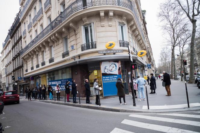 Rue Bayen, dans le 17e arrondissement de Paris, de nombreuses personnes font la queue sur le trottoir pour se rendre à La Poste, le lundi 16 mars.