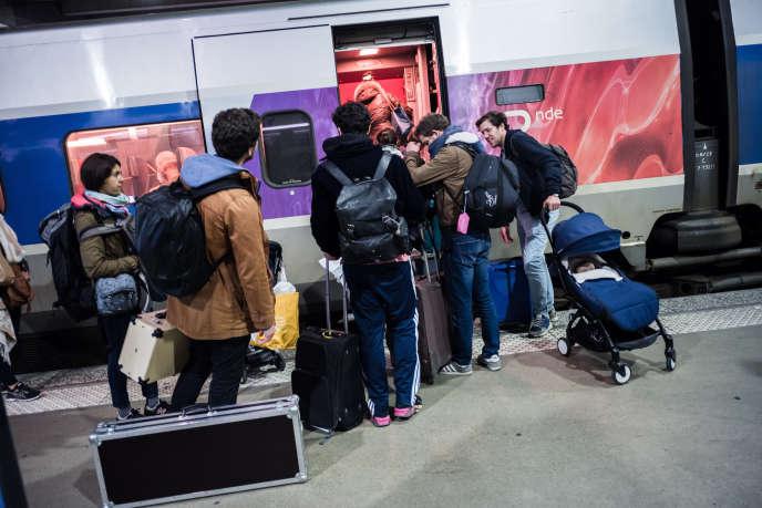 Des passagers montent dans le TGV en gare Montparnasse le 16 mars.