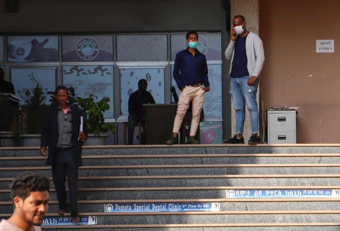 Des hommes portant des masques de protection se tiennent devant une cafétéria, après l'annonce du premier cas de Covid-19, à Addis-Abeba,le 13 mars 2020.