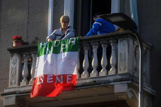Une femme installe un drapeau italien sur lequel on peut lire « tout ira bien» sur son balcon à Milan, le 16 mars.