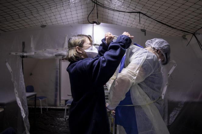 Une aide soignante aide un infirmier à s'habiller, à l'hôpital Henri-Mondor de Créteil, le mercredi 4 mars.