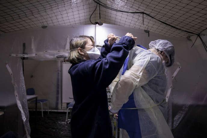 Une aide-soignante aide un infirmier à s'habiller, dans une tente installée à l'extérieur de l'hôpital Henri Mondor, à Créteil, depuis le 4 mars.