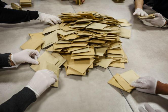 Des assesseurs et des citoyens volontaires procèdent au dépouillement des votes dans un bureau à Toulouse, dimanche 15 mars. En raison de l'épidémie de coronavirus, ils sont munis de gants de protection.