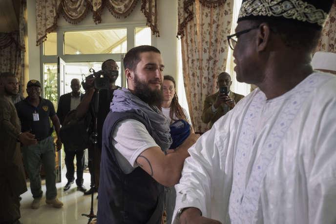 Luca Tacchetto et Edith Blais (en arrière-plan) sont accueillis par des officiels à leur arrivée à l'aéroport de Bamako, au Mali, le 14 mars 2020.