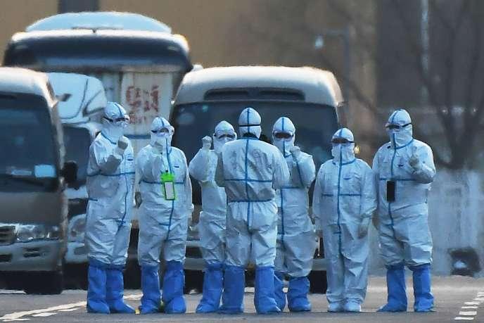 Des employés chinois prêts à escorter les passagers qui arrivent à Pékin vers le Parc des expositions où ils seront mis en quarantaine, le 17 mars.