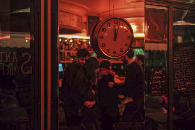 Des gens rassemblés dans un bar, avant la fermeture officielle à minuit de toutes les entreprises non essentielles, à Paris, le 14 mars.