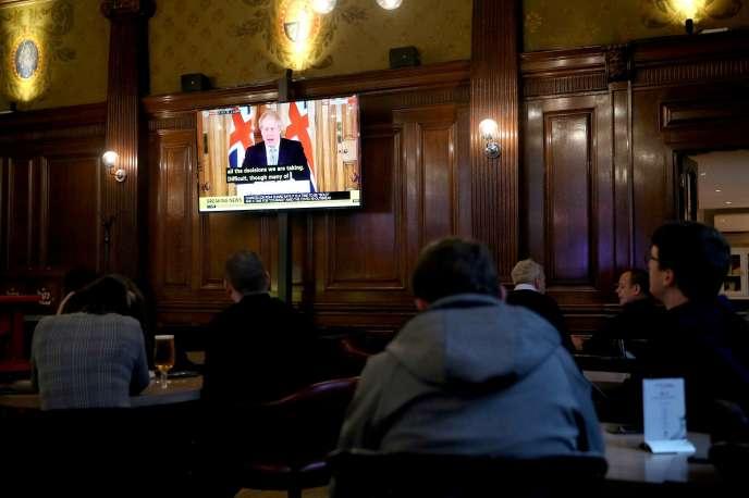 La conférence quotidienne du gouvernement britannique sur le coronavirus retransmise, mardi 17 mars, dans un pub de Londres.