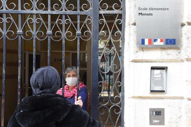 Une enseignante de cours élémentaire porte un masque en donnant des instructions sur les devoirs à un parent à Bordeaux le 17 mars.