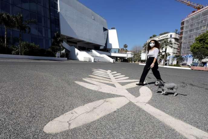 Une passante portant un masque marche, le 18 mars, près du Palais des festivals de Cannes qui ne pourra accueillir le célèbre festival de cinéma au mois d'avril.