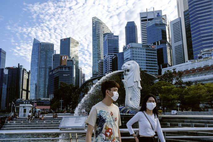 Devant la statue Merlion à Singapour, le 14 mars.