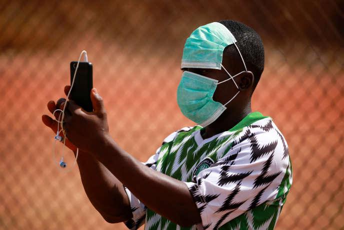 Un supporteur enregistre avec son téléphone l'un des derniersmatchs de football autorisés, à Abuja, au Nigeria, le 5 mars 2020.