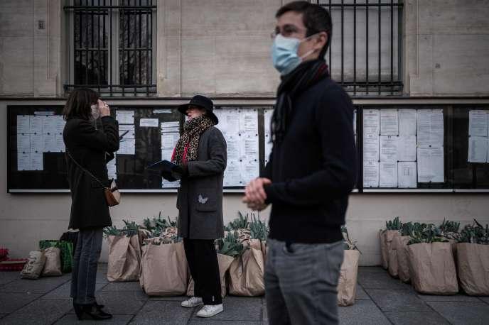 Des membres d'une AMAP distribuent des paniers de fruits et légumes, à Paris, le 18 mars.