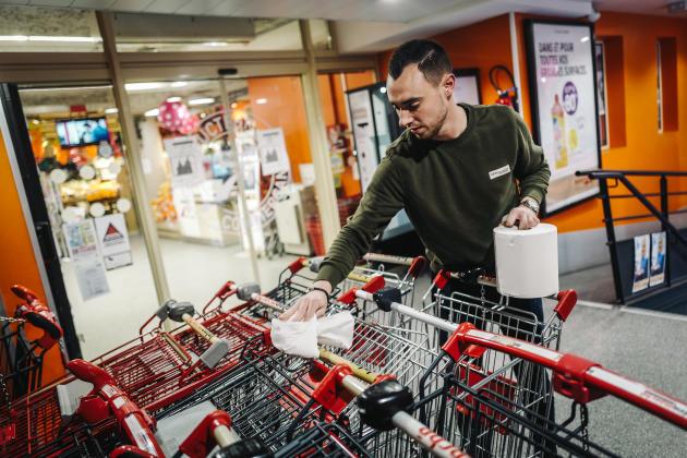 Romain, chef de caisse, nettoie les chariots pour les clients.