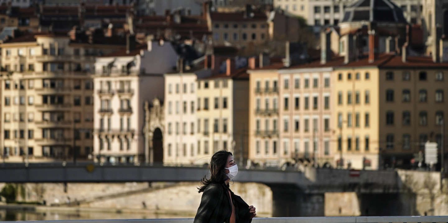 A woman wearing a mask walks along a bridge in the center of Lyon, central France, Wednesday, March 18, 2020. French President Emmanuel Macron said that for 15 days starting at noon on Tuesday, people will be allowed to leave the place they live only for necessary activities such as shopping for food, going to work or taking a walk. For most people, the new coronavirus causes only mild or moderate symptoms. For some it can cause more severe illness, especially in older adults and people with existing health problems. (AP Photo/Laurent Cipriani)