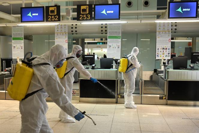 Des membres de l'Unité militaire d'urgence (UME) procèdent à une désinfection générale de l'aéroport international de Barcelone-El Prat, le 19 mars 2020.