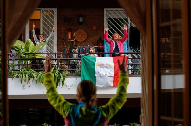 A Rome, des habitants confinés échangent de leur balcon, le 18 mars 2020.