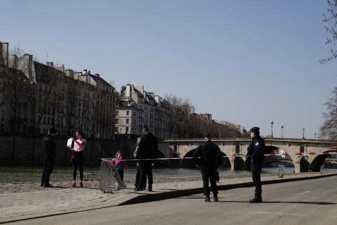 Des policiers contrôlent l'attestation présentée par une joggeuse, sur les quais de Seine, à Paris, le 19 mars.