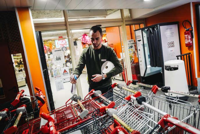Un chef de caisse nettoie les chariots avant l'ouverture du supermarché, à Issy-les-Moulineaux (Hauts-de-Seine), le 18 mars.