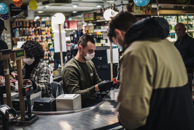 Un caissier travaille dans un Intermarché à issy-Les-Moulineaux dans les Hauts de Seine, le 18 mars 2020. Le supermarché ouvre exceptionnellement de 8h à 8h30 uniquement pour les clients de plus de 70 ans, pour répondre aux besoins en plein confinement provoqué par l'épidémie de Coronavirus. Lucas Barioulet pour Le Monde