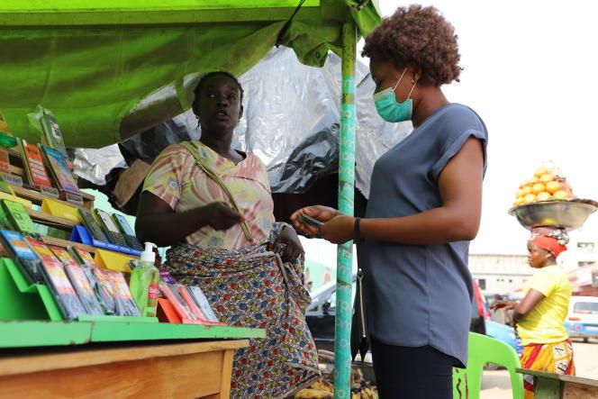 Au marché d'Anono à Abidjan, où Esther, vendeuse de téléphones, s'inquiète des mesures prises par le gouvernement et d'un potentiel confinement, en mars.