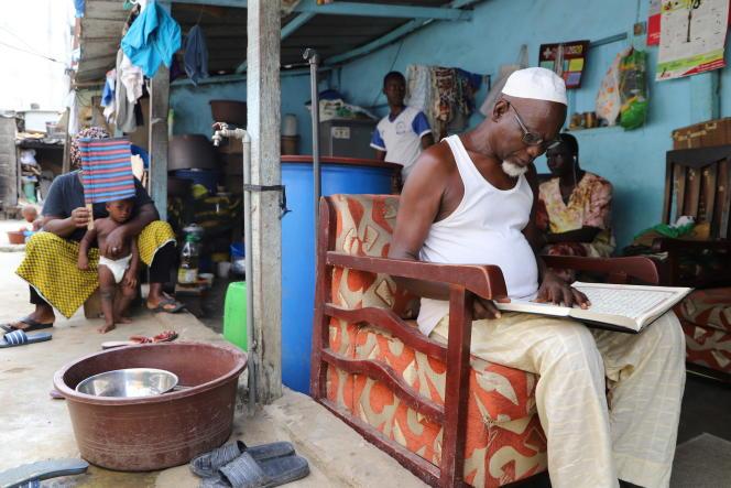 Dans la cour familiale d'Ousmane (en tee-shirt blanc et bleu, en arrière plan), en compagnie de sa famille et de ses voisins, en mars.