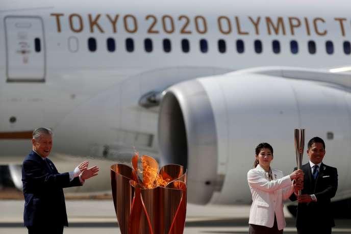 Les anciens champions olympiques Saori Yoshida et Tadahiro Nomura (à droite) ont allumé le chaudron olympique, aux cotés de Yoshiro Mori, président de Tokyo 2020, vendredi 20 mars sur le tarmac de l'aéroport d'Higashimatsushima.