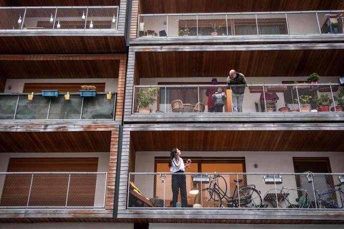 Des voisins échangent quelques mots depuis leurs balcons, un verre à la main, à Paris, le 20 mars 2020.