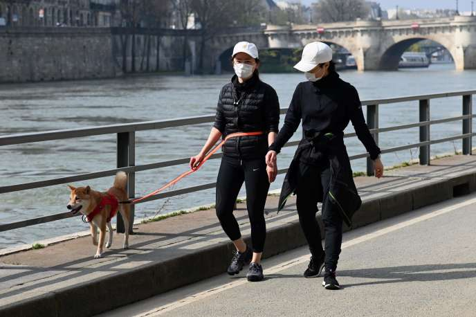 Deux femmes portant un masque protecteur marchent le long des rives vides de la Seine, au 4e jour de confinement, à Paris, le 20 mars.