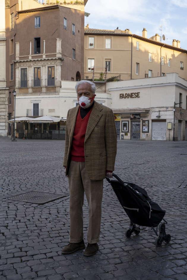 Sur le Campo dei Fiori, une place d'ordinaire très agitée du centre de la ville, un Romain se rend chez son médecin après avoir fait quelques courses. Rome, le 18 mars.